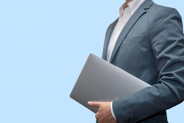 パソコンを抱えたスーツの男性